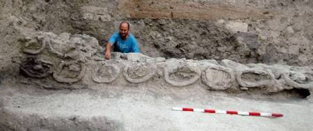 An archaeologist indicates the opening of one of the ancient beehives found in excavations in Rehov in Israel.